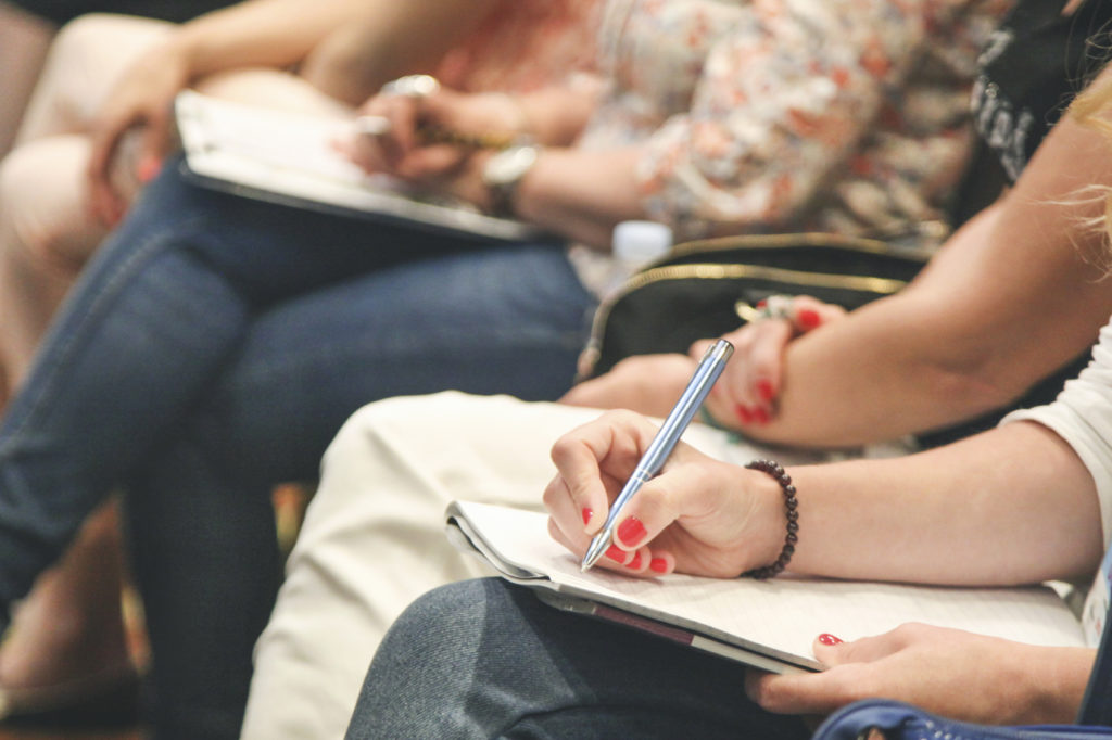 Unrecognizable woman taking notes at a seminar or business meeting